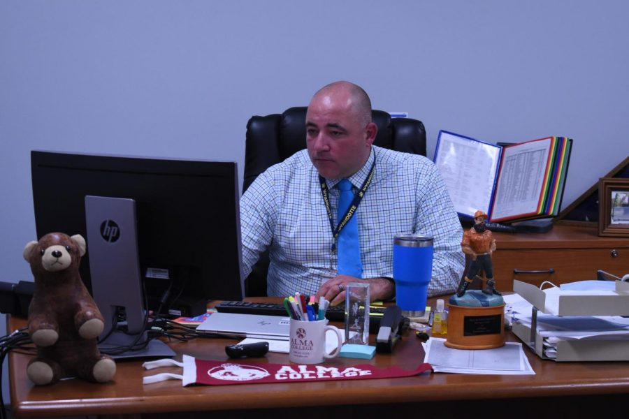 Principal Ben Reynolds checks emails and memos in his office.