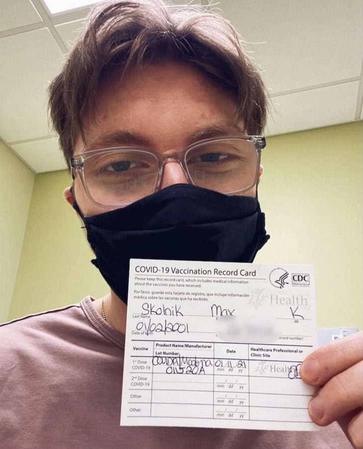 Skolnik+poses+with+a+card+certifying+that+he+received+the+Moderna+vaccine.