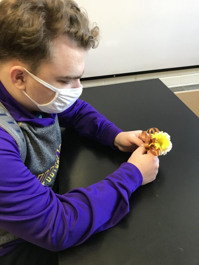 Senior Brandon Chaaban, a Botany student, works on a corsage in class. In previous years before COVID, students would be doing more extensive work processing and arranging flowers for orders from Teddy's.