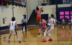 Junior Ethan Breaux jumps to shoot the ball but is blocked by Lincoln Park's number 15 mid air. The two collided resulting in a foul on the rail splitters.