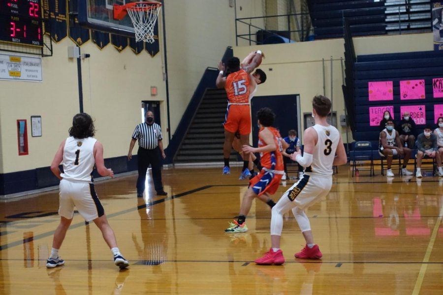 Junior Ethan Breaux jumps to shoot the ball but is blocked by Lincoln Parks number 15 mid air. The two collided resulting in a foul on the rail splitters.