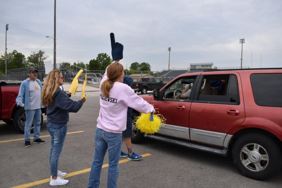 RHS staff and parents cheer on Class of 2021 seniors as they exit their senior class drive thru.