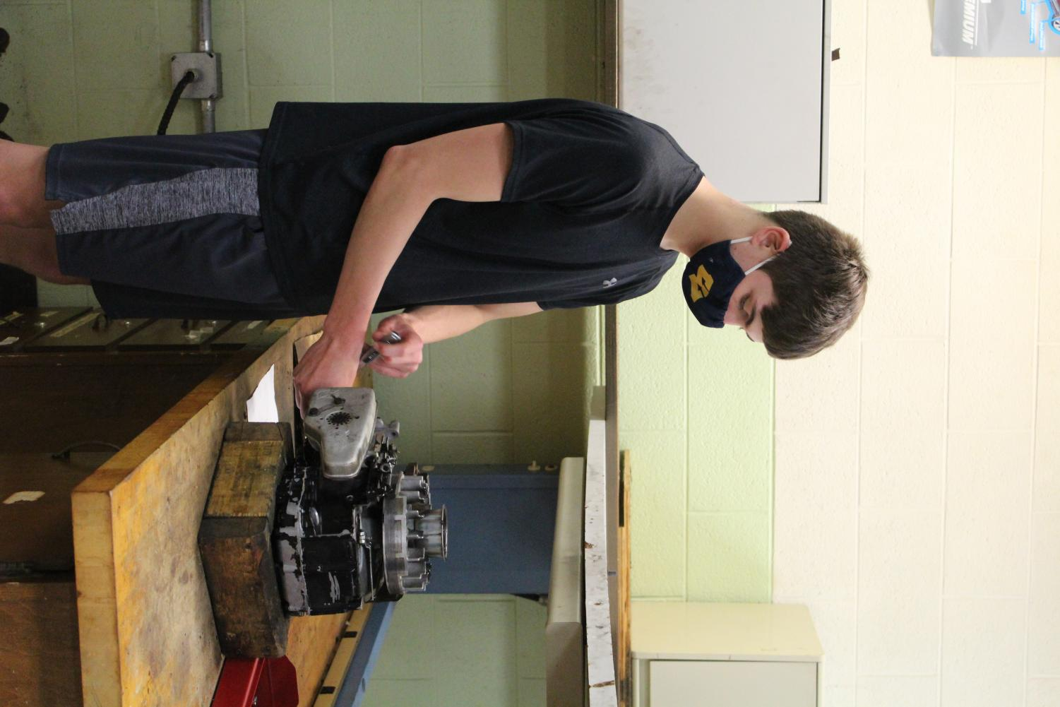 Class of 2023 treasurer Caden Suave working on a machine in beginners auto.