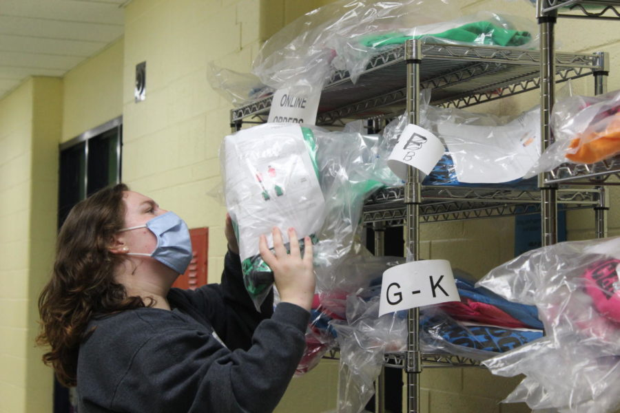 Senior DECA member, Elizabeth Richardson, sorts through Block Out Cancer merchandise in order to distribute it to the community.