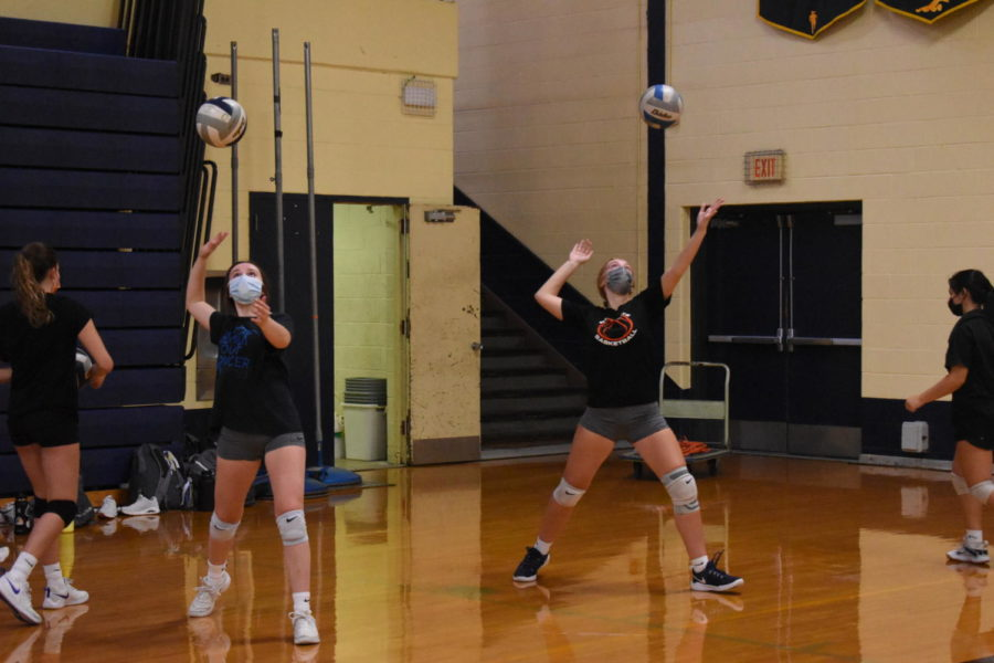 Volleyball players Megan Powell and Avery Patrick practicing social distancing during their serving drills while wearing masks per the Wayne County Health Department's regulations.