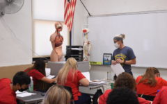 Rooney checks up on students work while they work on different references for the body.
