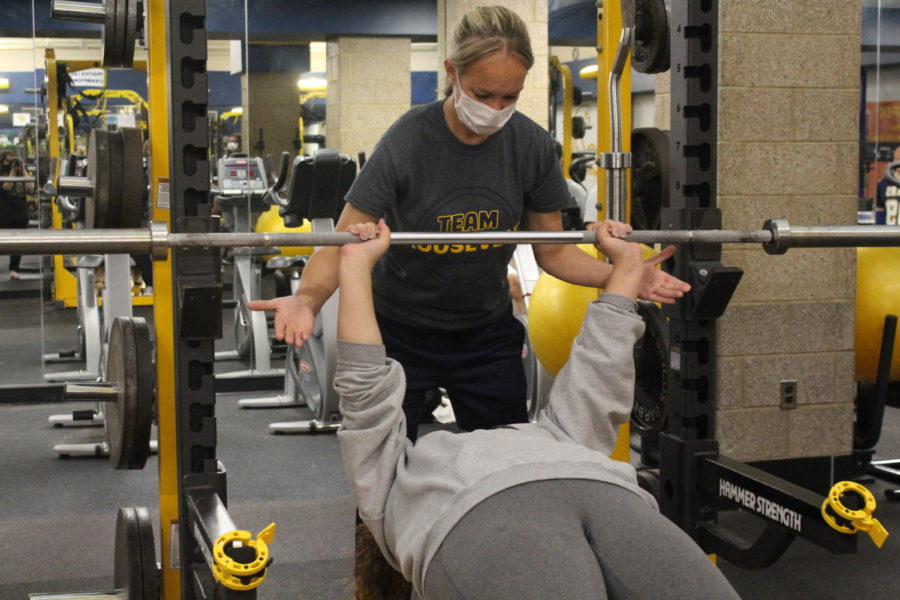 Gym teacher Rebecca Gardocki shows students how to properly and safely use benching equipment.