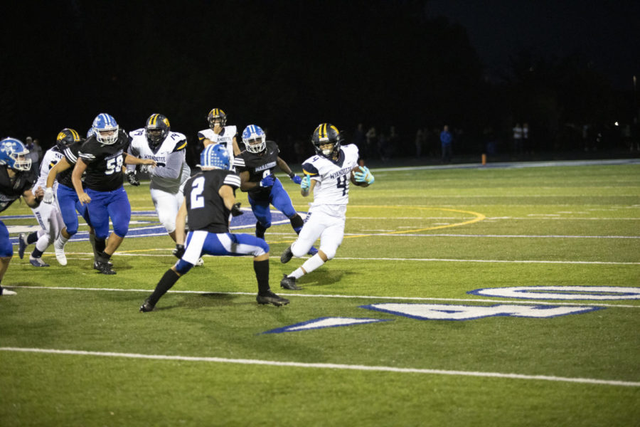 Running the ball, junior running back Elvis Valverde tries to keep the ball in Wyandottes possession.